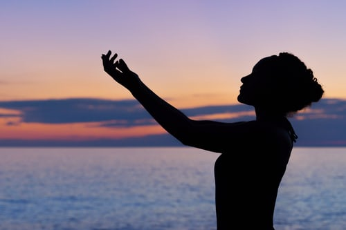 photo of girl lifting hands to sky